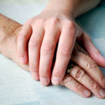junge Hand streicht alte Hand
